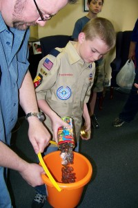 Boy Scout empties change jar into bucket