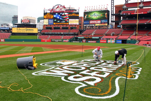 Workers paint a 2011 World Series logo on the field at Busch Stadium