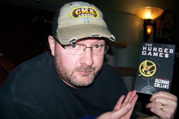 "Todd Harding with a copy of ""The Hunger Games"""