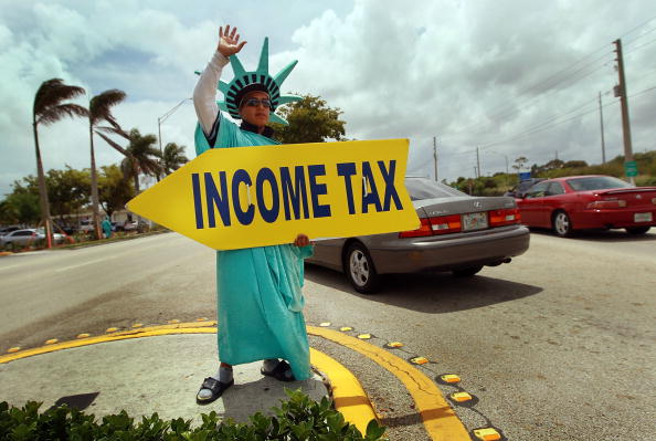 Guy in Statue of Liberty Costume holds Income Tax sign