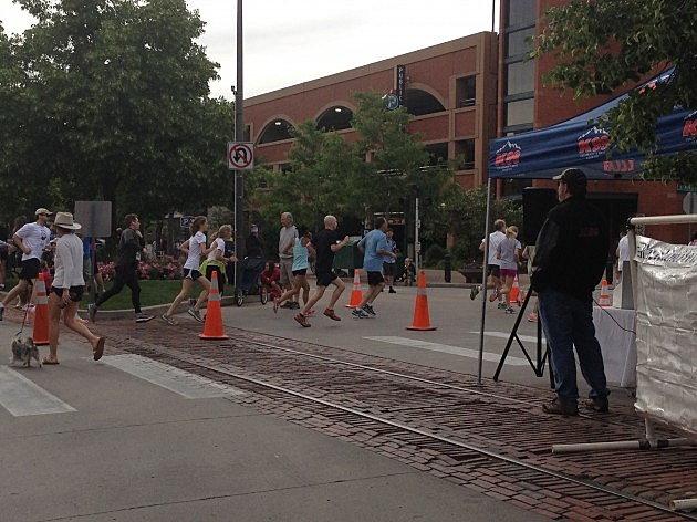 Runners pass by as Todd watches Father's Day 5K