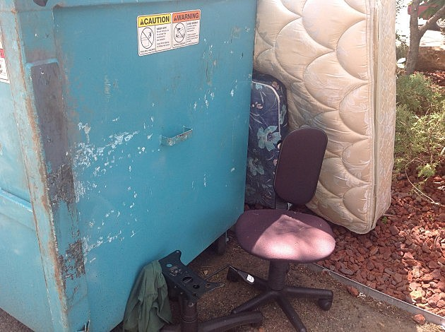 Dumpster with mattresses and old chairs
