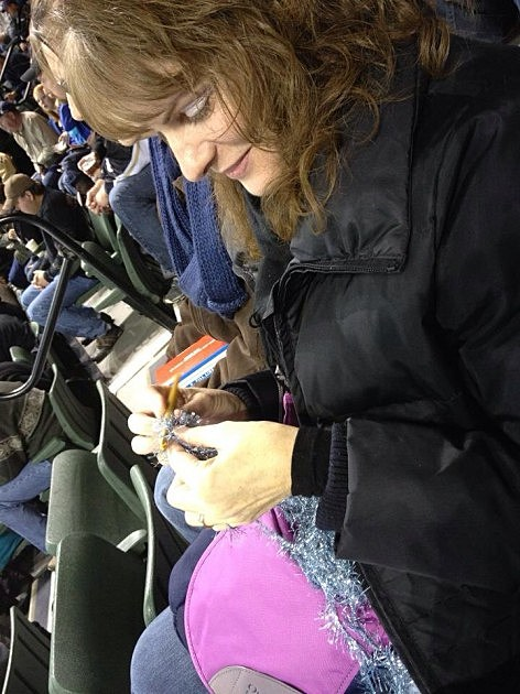 Todd's wife Jenny Crocheting at Colorado Eagles Hockey game