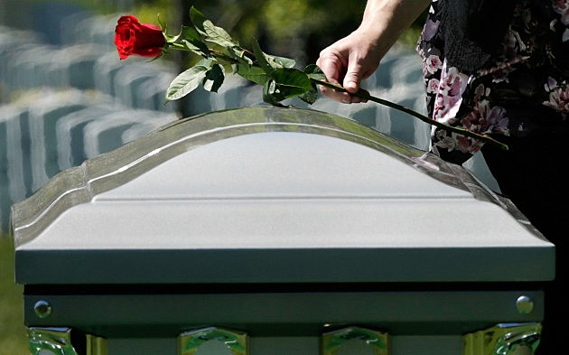 A person places a rose on a casket