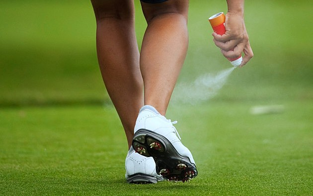 Female golfer sprays mosquito repellent on her leg