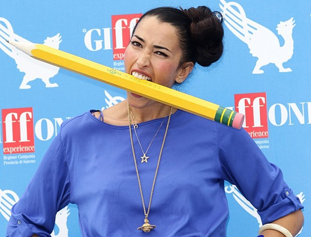 Woman with big pencil in mouth