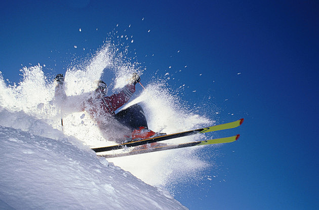 Low angle view of a skier throwing up snow while skiing on a mountain